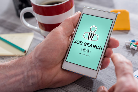 Male hand holding a smartphone with job search concept