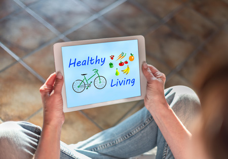 Woman sitting on the floor with a tablet showing healthy living concept