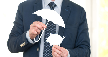 Concept of money protection with financial advisor holding an umbrella over a piggy