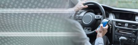 Man using a smartphone while driving a car. panoramic banner
