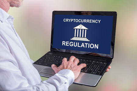 Man using a laptop with cryptocurrency regulation concept on the screen Stockfoto