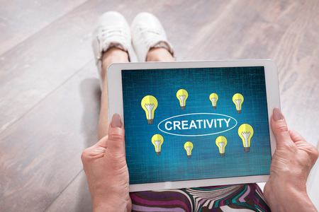 Woman sitting on the floor with a tablet showing creativity concept