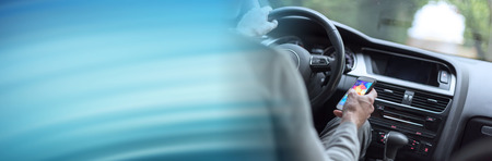 Man driving using smartphone. panoramic banner