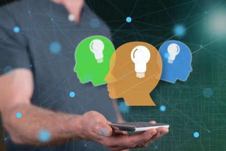 Human brain ideas concept above a smartphone held by a man in background