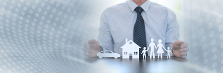 Insurer protecting a family, a house and a car with his hands. panoramic banner