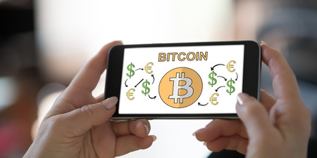 Hand holding a smartphone with bitcoin concept