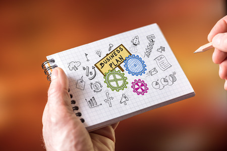 Hand drawing business plan concept on a notepad