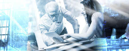 Young businesswoman and senior businessman working together at office; multiple exposure Stock Photo