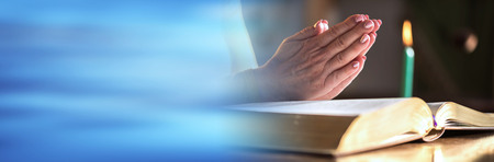 Close up of woman praying with her hands over the bible, hard light. panoramic banner Foto de archivo