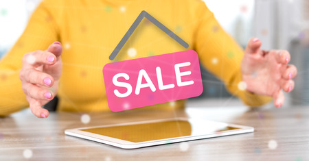 Digital tablet with sale concept between hands of a woman in background