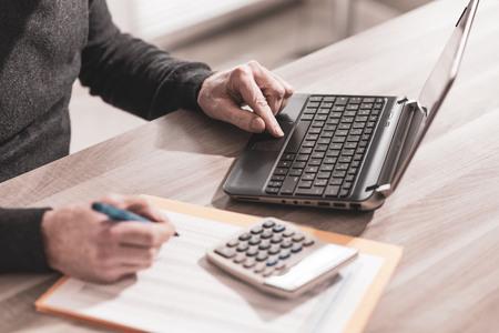 Männlicher Buchhalter, der am Laptop arbeitet Standard-Bild