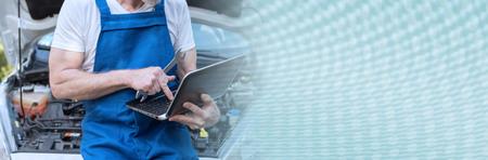 Car mechanic using laptop for checking car engine. panoramic banner
