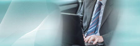 Businessman using his laptop while traveling. panoramic banner Stock Photo