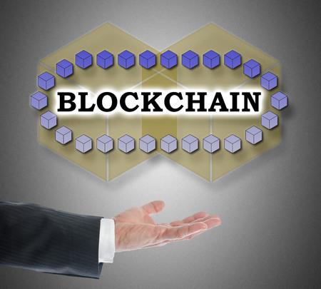 Blockchain technology concept levitating above a hand on grey background Foto de archivo