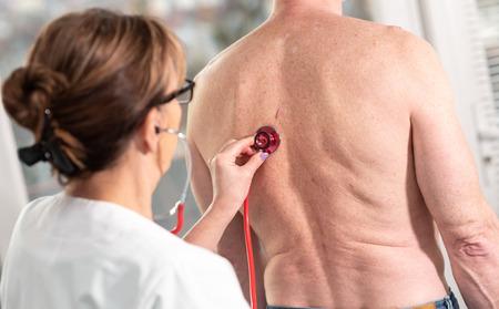 Female doctor using stethoscope to exam patient Foto de archivo