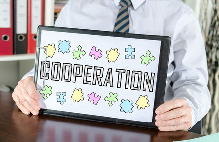 Cooperation concept shown by a businessman Imagens