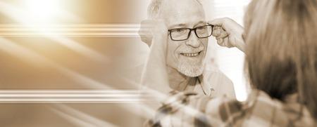 Senior man testing new eyeglasses in optician store; light effect