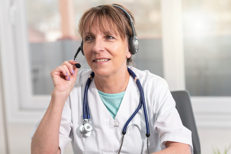 Portrait of mature female doctor during online medical consultation