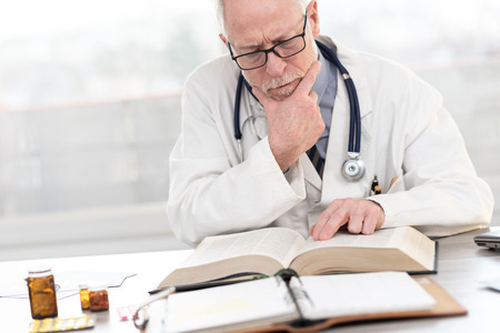 Senior doctor reading a textbook in medical office