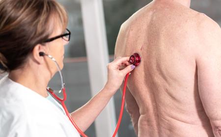 Doctora con estetoscopio para examinar al paciente
