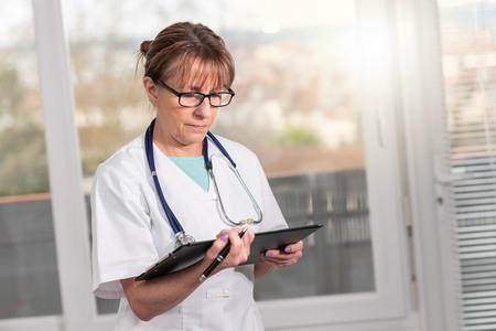 Ärztin, die Notizen in der Zwischenablage steht und liest Standard-Bild