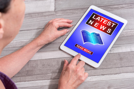 Woman using a tablet showing latest news concept