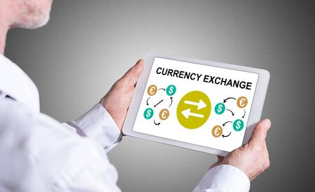 Man holding a tablet showing currency exchange concept Stock Photo