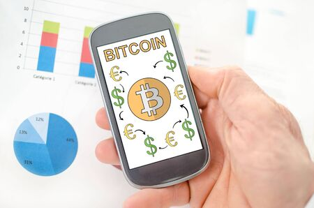 Bitcoin concept on a smartphone held by a hand Stock Photo