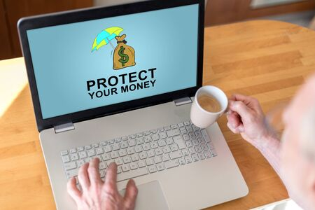 Man using a laptop with money protection concept on the screen Stock Photo