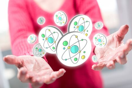 Nuclear research concept above the hands of a woman in background