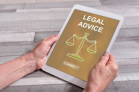 Female hands holding a tablet with legal advice concept Stockfoto