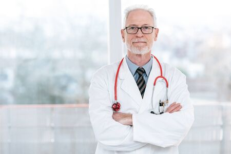 Portrait of senior doctor with arms crossed Stockfoto
