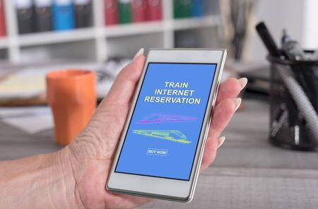 Female hand holding a smartphone with train internet reservation concept Reklamní fotografie