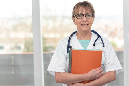 Portrait of female doctor standing and holding a folder