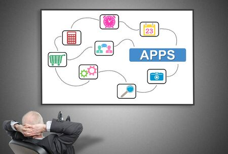 Relaxed businessman looking at apps concept on a whiteboard Stock Photo