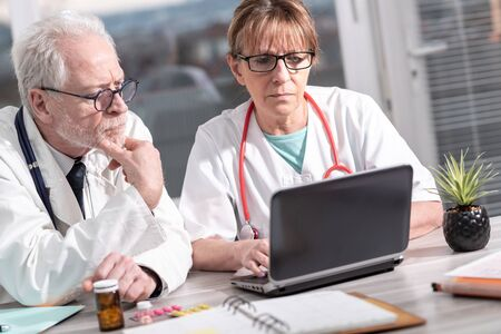 Two mature doctors discussing about medical report on laptop Stock Photo