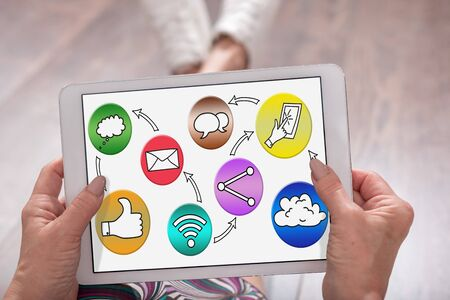 Social media concept shown on a tablet held by a woman