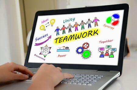 Hands on a laptop with screen showing teamwork concept Reklamní fotografie