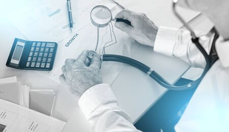 Businessman holding a stethoscope and a magnifying glass over a graph showing growth Reklamní fotografie