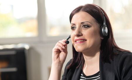 Portrait of smiling female phone operator with headset Imagens