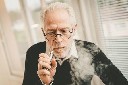 Retrato, de, hombre mayor, fumar, cigarrillo electrónico