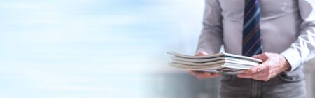 Hands of businessman holding magazines. panoramic banner Archivio Fotografico