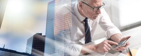 Businessman doing his accounting with calculator; multiple exposure