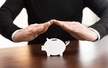 Male hands having a protective gesture of a piggy bank