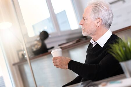 Thoughtful senior businessman looking out of window during coffee break