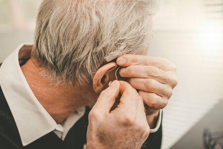 Senior man putting hearing aids