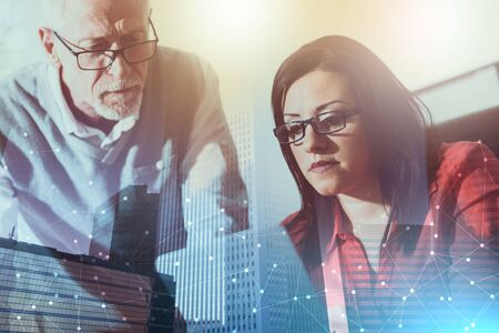 Young businesswoman and senior businessman working together at office, light effect; multiple exposure Stock Photo