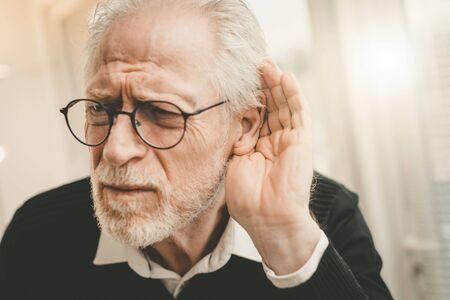 Retrato, de, hombre mayor, teniendo, problemas auditivos Foto de archivo
