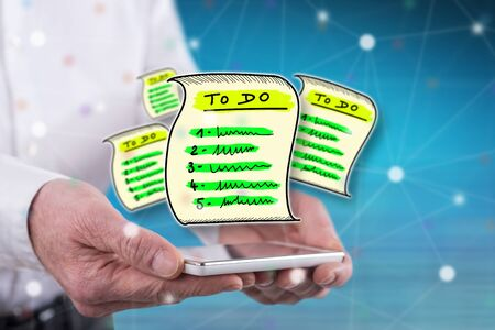 To do list concept above a smartphone held by hands