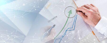 Geschäftsmann, der eine Lupe über einem Diagramm hält, das Wachstum zeigt; mehrfache Belichtung Standard-Bild